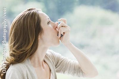 Frau mit Asthmaspray - bei entzündlichen Erkrankungen wie Asthma neigt das Blut zur Gerinnselbildung. Deshalb steigt das Risiko für eine Thrombose und Embolie.
